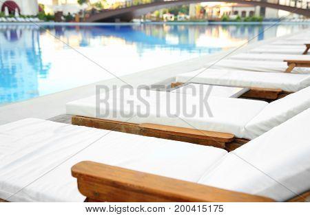 Empty sunbeds near swimming pool in luxury hotel