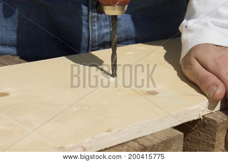 The carpenter drills a hole in the board.