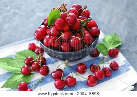 Bowl with fresh ripe cherries on napkin