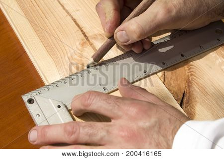 The carpenter's hands indicate the dimension on the board with a pencil and an angle