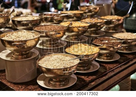 Different kinds of dry breakfast in bowls on table at buffet