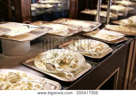 Plates with different kinds of cheese on table at buffet
