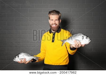 Handsome seller holding fresh fish on gray wall background