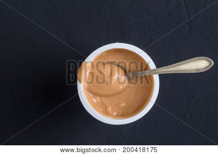 Yogurt background top view shot of caramel flavoured yoghurt in plastic cup with small silver spoon isolated on black background - close up image with space for text