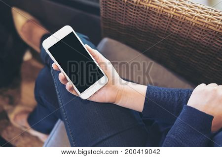 Mockup image of a woman's hand holding white mobile phone with blank black screen on thigh sitting on a couch