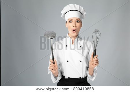 Young female chef with utensils on light background