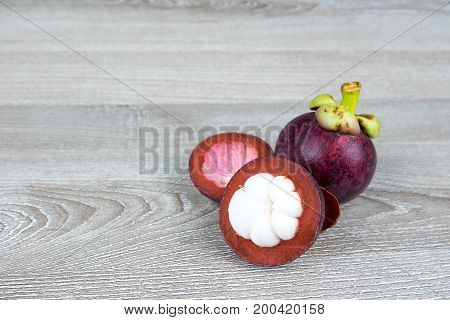Mangosteen cut off one side on wooden table background Mangsteen is the queen of fruits in Thailand.