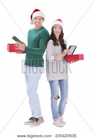 Happy young couple in Christmas hats holding gift boxes, on white background