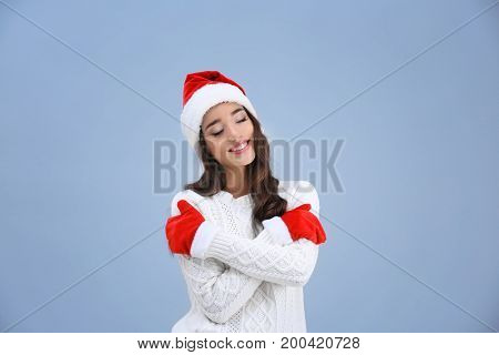 Beautiful emotional woman in Christmas hat and red winter gloves on color background