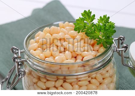 jar of canned white beans on grey place mat - close up