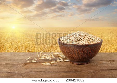 uncooked oatmeal in bowl and oat ears on table with ripe cereal field on the background. Golden field on sunset. Agriculture and harvest concept. Healthy eating for diet and vegan