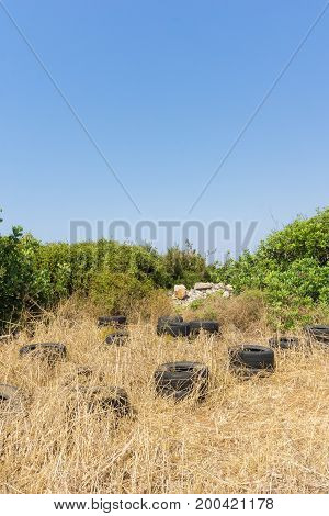 View on a dried up Field and black Tyres in Summer. Close-up of some Tyres in the middle of the nature. Natural Background