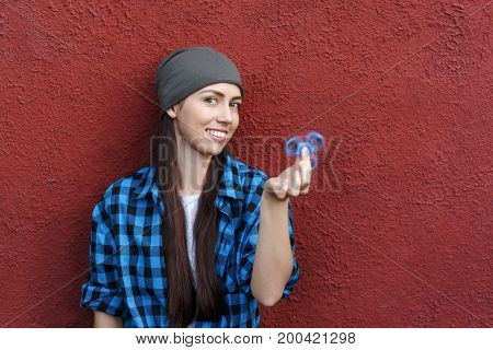 happy hipster girl playing with fidget spinner. Portrait of young woman holding spinner. Popular trendy stress relieving toy. Copy space