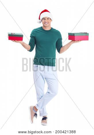 Handsome man in Christmas hat holding gift boxes on white background