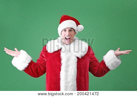 Handsome man in Santa Claus costume on color background