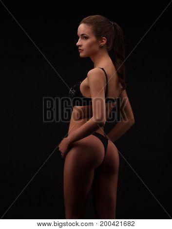 Woman In Black Lingerie On Dark Studio Background. Slim Girl With Nice Ass Posing.