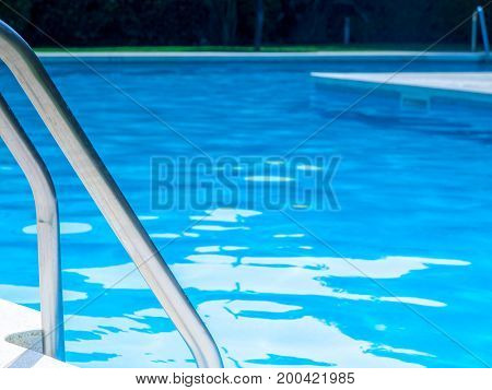 Swimming pool with Steel ladder and blue water