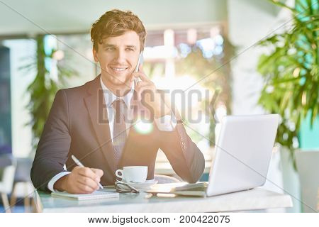 Portrait of handsome young businessman speaking by phone and smiling while working in sunlit cafe during coffee break
