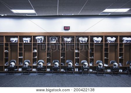 American Football locker room in a large stadium. Helmets sitting on chairs and jersey`s resting in the lockers