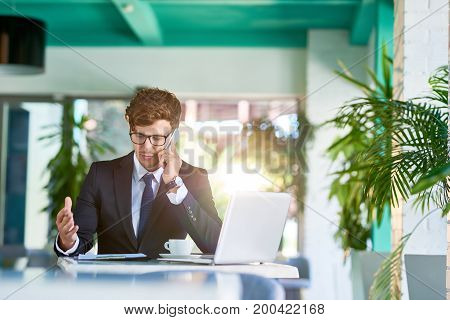 Portrait of handsome young businessman speaking by phone explaining plan to partner while working in sunlit modern office