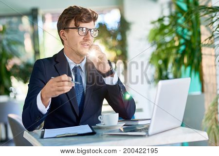 Portrait of successful young businessman speaking by phone selling services to customer while working in sunlit cafe during coffee break