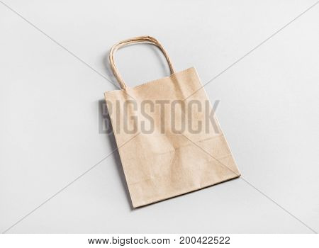 Photo of paper shopping bag on paper background. Craft paper package.