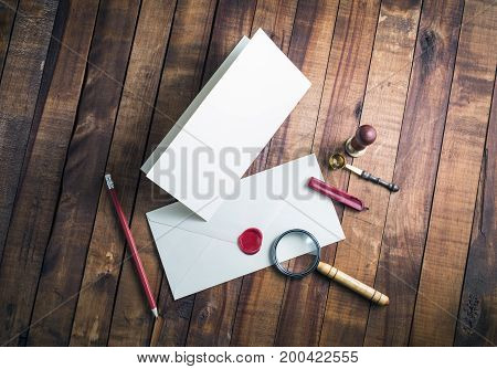 Photo of blank stationery set on vintage wood table background. Still life with postal accessories. Template for your design. Top view.