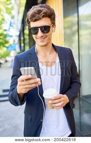 Portrait of handsome young man smiling happily using smartphone while walking in city streets holding paper coffee cup