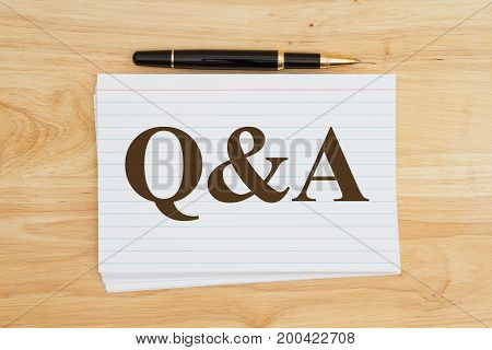 Writing your questions and answers Stack of white index cards on wood desk with a pen with text Q&A