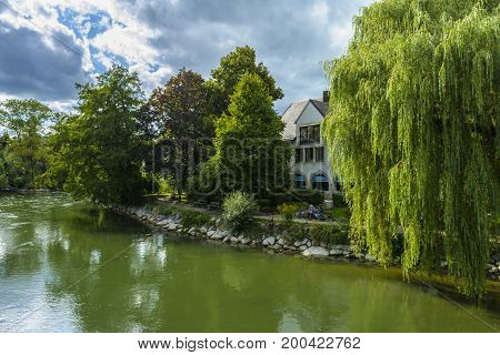 Evening view with unidentified people who relax on a bench near the Amper river on September 06, 2015 in Furstenfeldbruck Germany.