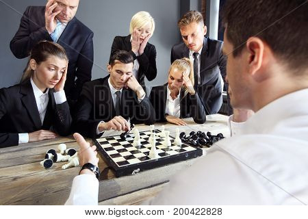 Business people playing chess team of workers losing leader is winning