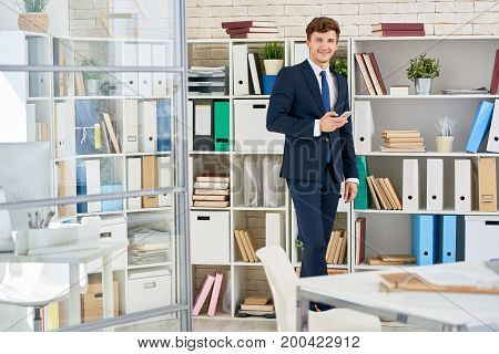 Portrait of successful young businessman posing in modern office standing against book cases holding smartphone and smiling to camera