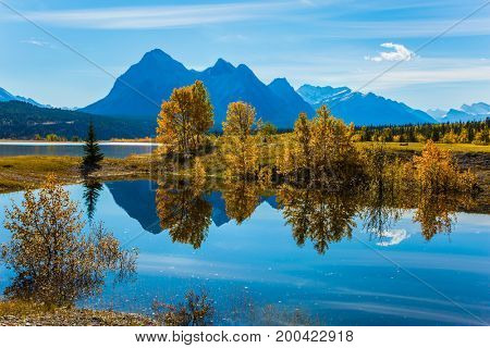 The mirror surface of the magnificent artificial lake Abraham reflects light cirrus clouds and trees. A sunny autumn day in the Rocky Mountains of Canada. The concept of ecological and active tourism