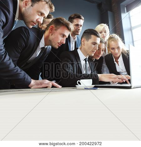 Business team look together at one laptop copy space