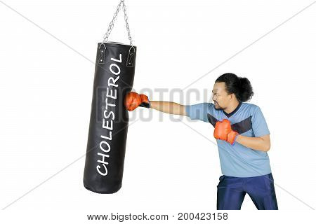Picture of young African male punching a word of cholesterol on the black sack isolated on white background