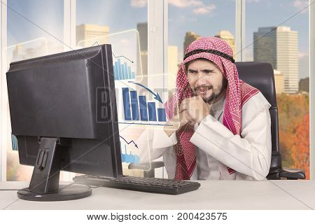 Portrait of middle eastern male entrepreneur is feeling confused while looking at a declining business graph on the monitor with autumn background on the window