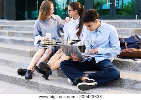 Teenage students having fun at break: pretty girls chatting animatedly with each other while sitting on stairs of modern school building, their handsome classmate browsing Internet on laptop