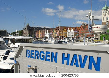 Bergen, Norway - July 2014: View to Bryggen houses, Bergen's landmark, with private boats and people on the waterfront