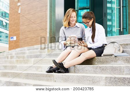 Pretty friends in school uniform looking through photos on mobile phone while waiting for beginning of lesson outdoors, facade of modern building on background