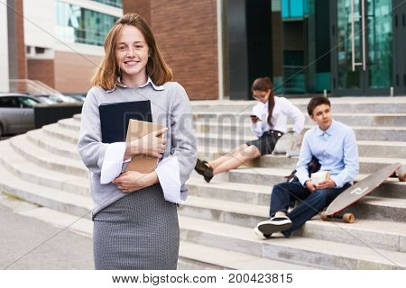 Portrait of pretty fair-haired student looking at camera with charming smile while standing in front of modern school building, she holding textbooks in hands