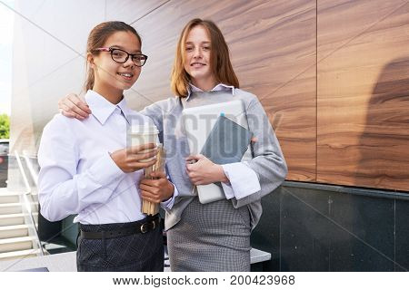 Group portrait of smart teenage students holding piles of textbooks in hands and posing for photography with toothy smiles while spending break at lounge
