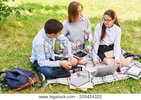 Group of teenagers gathered together at sunny park and discussing details of their joint school project, they refreshing with fizzy drink