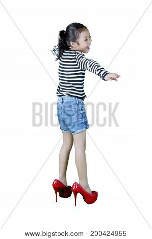 Full length of a cute girl trying her mother's shoes while standing in the studio isolated on white background