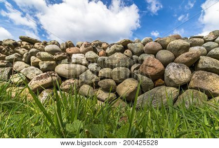 Old Stone wall buildt from the stones of the moraine Raet. With green grass in front and blue sky with clouds above, from Jomfruland, Norway
