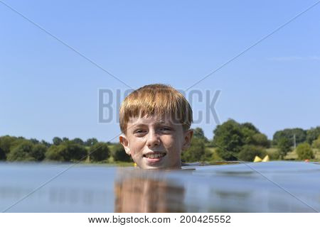 Young auburn haired boy treading water in a lake