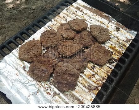 many hamburgers cooking on a grill with foil