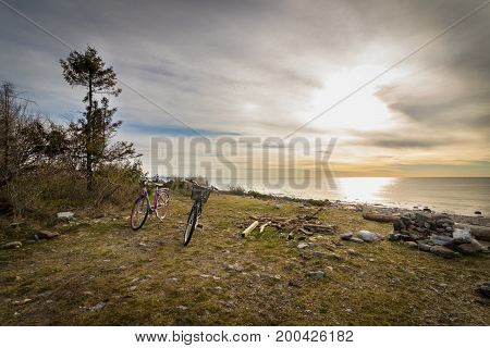 Two bicycles standing at the grass at the beach. Ocean view from the pebble shore in the island of Jomfruland in Jomfruland National Park, Kragero, Norway. Jomfruland, meaning Virgin Land in Norwegian, is part of Raet, a big moraine from the ice age.