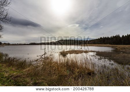 Sun behind clouds over a lake in spring, at Gjennestadvannet, Stokke, Vestfold in Norway