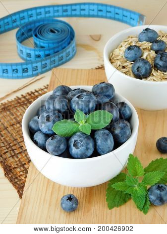 Blueberries in a white bowl and measuring tape in the background
