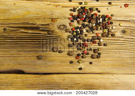 Mixture Of Peppers Spice On Wooden Table